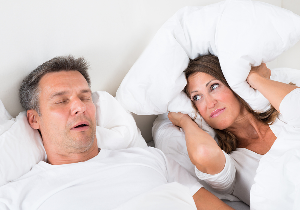 snoring man in bed next to annoyed wife